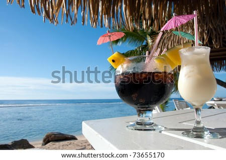Pina Colada and Island surprise cocktails on a table by the beach at a resort in Rarotonga in the Cook Islands - stock photo