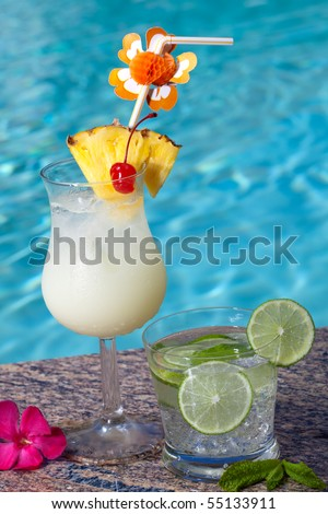 Pina Colada and Mojito cocktails on swimming pool side - stock photo