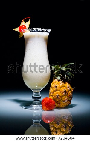 Pina Colada cocktail with cherry surrounded by pineapple and strawberry