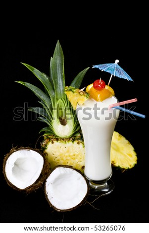 Pina Colada over black background, garnished with slice of pineapple and coconut. - stock photo