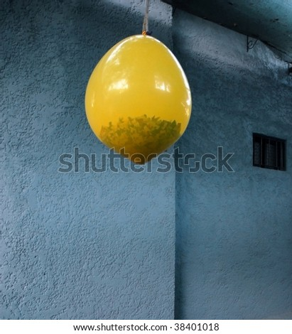 Pinata. Hanging yellow balloon with gifts and confetti inside. Rough wall texture background - stock photo