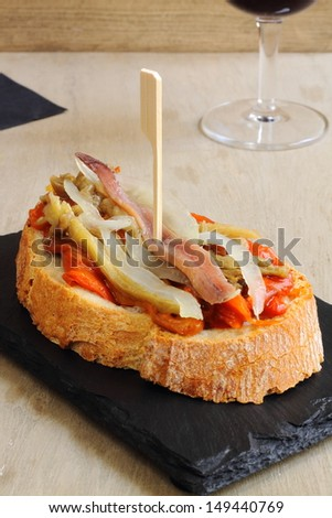 Pinchos or pintxos, traditional Spanish tapas made with small slices of bread topped with escalivada (roasted eggplant, onion, bell peppers and anchovies) and fastened with a skewer - stock photo