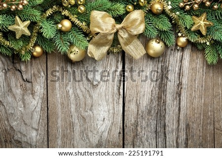 Pine branch and golden Christmas balls on wooden background - stock photo