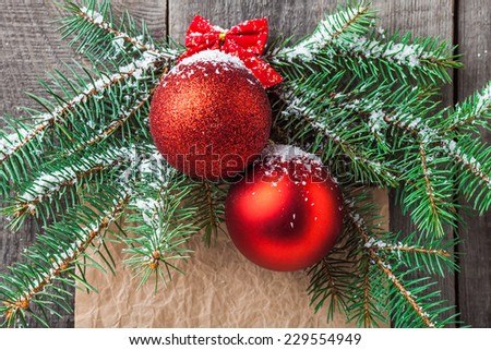 Pine branch and red Christmas balls on wooden background. Copy space - stock photo