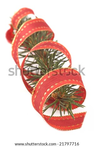 Pine branch with a red christmas ribbon isolated on white