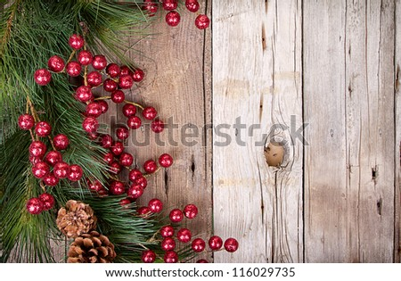 Pine branches with Christmas berries on wooden panels - stock photo