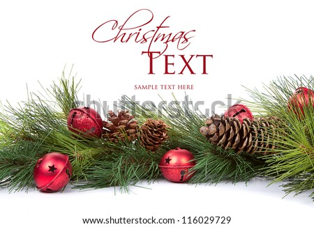 Pine branches with Christmas ornaments on white - stock photo