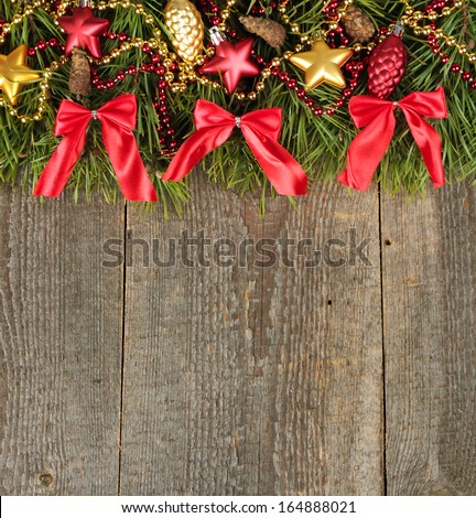 Pine branches with different Christmas baubles on old wooden background - stock photo