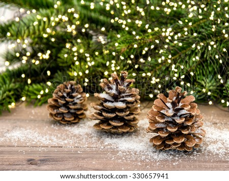 Pine cone and christmas tree branches. Festive decoration with colorful lights