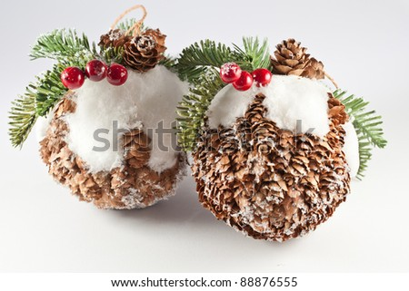 Pine cone christmas balls whit leaves, snow and berry on top. Isolated studio shot with white background
