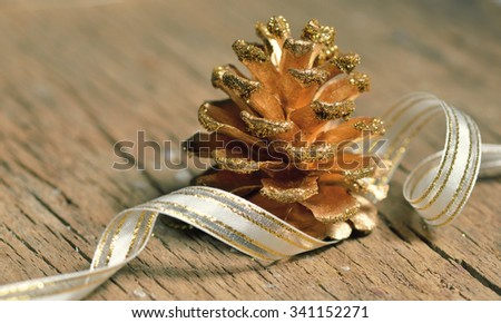 Pine cones and ribbon on wooden background - stock photo