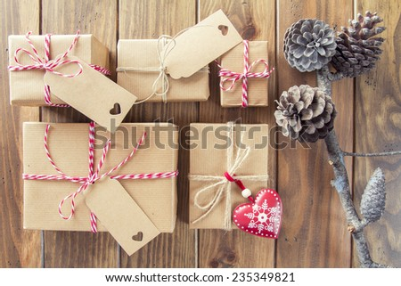 Pine cones and some paper parcels wrapped tied with tags. A red heart and some christmas gift boxes wrapped with paper kraft and tied with red & white baker's twine on a wooden table. Vintage Style. - stock photo