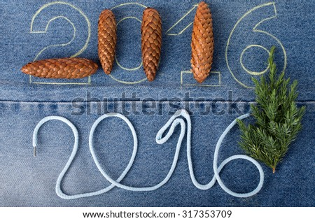 Pine cones, fresh branch of christmas tree and the numbers 2016 of rope and chalk contour on the background of the jeans. Christmas theme - stock photo