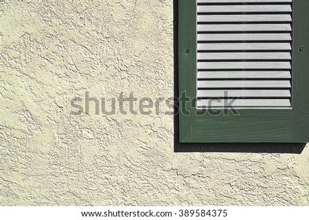 Pine green shutter on stucco exterior wall - stock photo