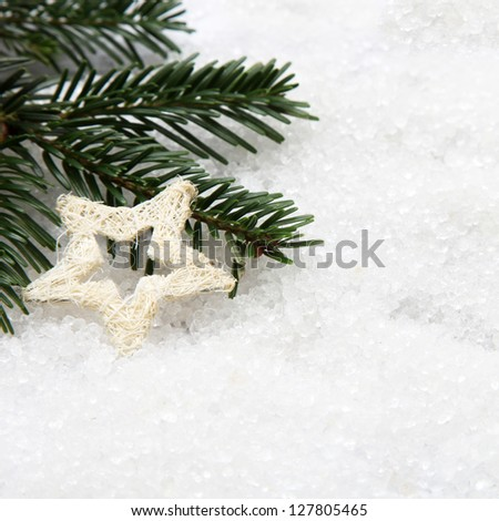 Pine needles and a white star Christmas ornament on snow