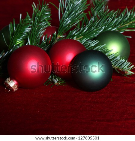 Pine needles and red and green Christmas baubles - stock photo