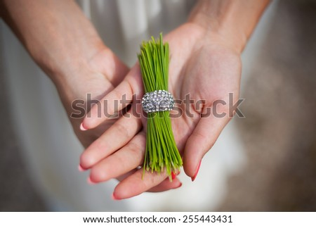 pine needles with a ring in the hands of a girl - stock photo