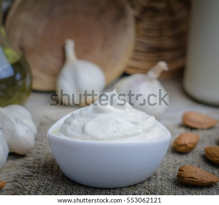 Pine nut mayonnaise or soy almond homemade vegan garlic mayo or bechamel white sauce on rustic rural wooden background.