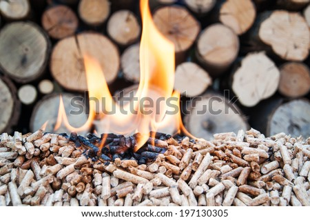 Pine pellets in flames- behind flames ara fire wood - stock photo