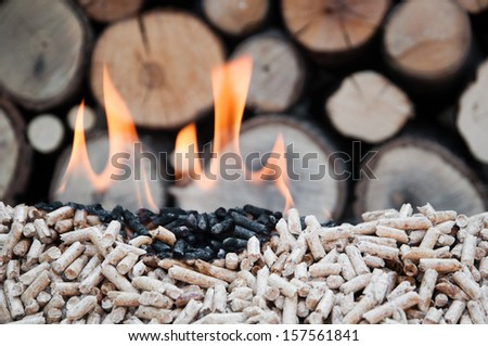Pine pellets in flames- selective focus on the heap - stock photo