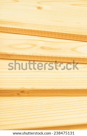 Pine planks stacked and ready for some carpentry job or woodworks. Close up with selective focus and shallow depth of field. - stock photo