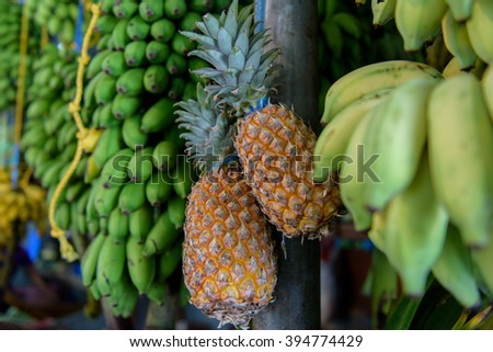 Pineapple and bananas on fruit market - stock photo