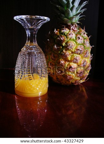 Pineapple and juice in the turned glass. - stock photo