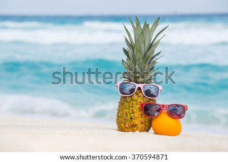 Pineapple and orange fruits in sunglasses on sand against turquoise caribbean sea water. Tropical summer vacation concept - stock photo