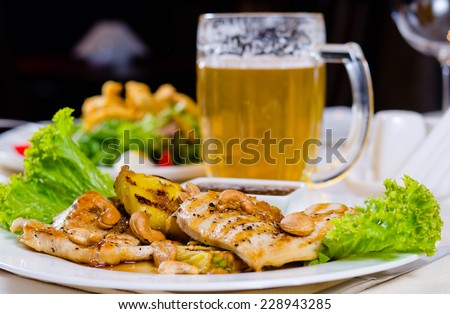 Pineapple Cashew Chicken Dish with Mug of Beer on Restaurant Table - stock photo