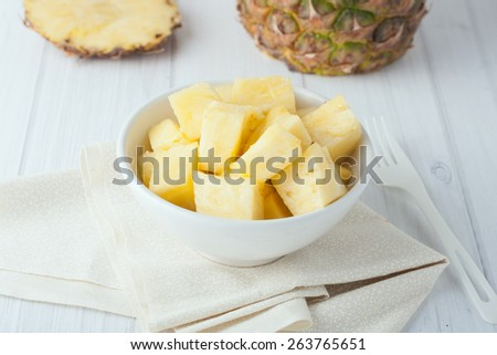pineapple chunks in white bowl on yellow napkin with pineapple pieces at the background - stock photo
