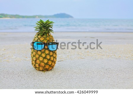 Pineapple fruit in sunglasses on sand against turquoise andaman sea water. Tropical summer vacation concept. Hipster pineapple with sunglasses on beach - fashion in summer - stock photo