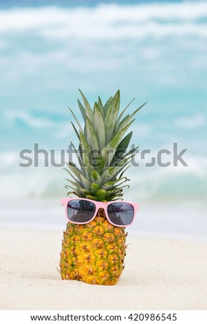 Pineapple fruit in sunglasses on sand against turquoise caribbean sea water. Tropical summer vacation concept - stock photo