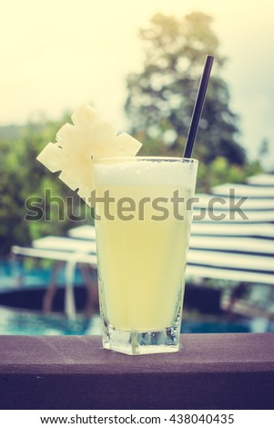Pineapple juice in glass with beautiful outdoor swimming pool in hotel resort - Vintage Filter and Sunflare Processing