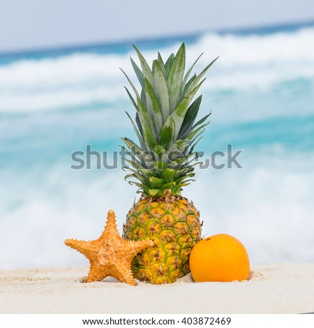 Pineapple, orange fruit and starfish on sand against turquoise caribbean sea water. Tropical summer vacation concept - stock photo