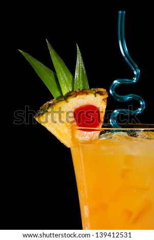 pineapple slice with a red cherry on the rim of a glass with a tropical drink