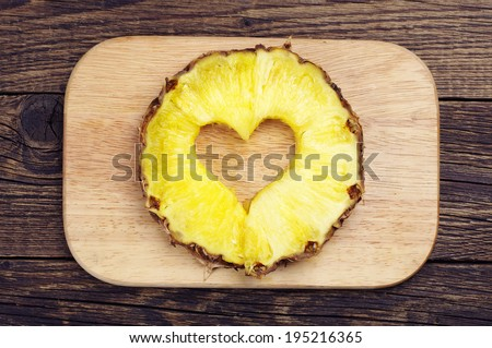 Pineapple slices with a cut in the shape of hearts on a cutting board - stock photo