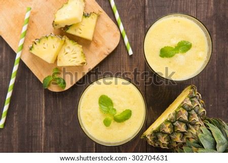 Pineapple smoothie with fresh pineapple on wooden table. - stock photo