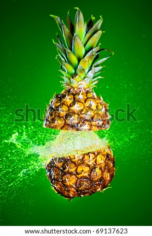 Pineapple splashed with water on a green background - stock photo