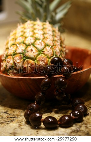 pineapple with a kukui nut lei in a bowl - stock photo