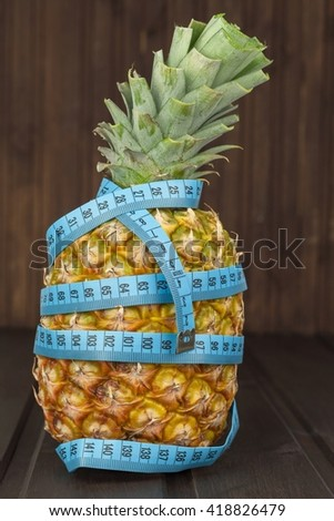 Pineapple with a measuring tape around. Ripe pineapple on a brown wooden background. Diet food. - stock photo