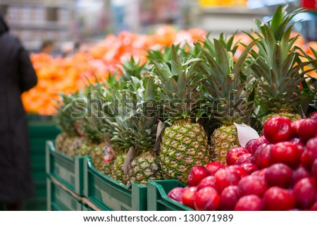 Pineapples and plums on boxes in supermarket - stock photo