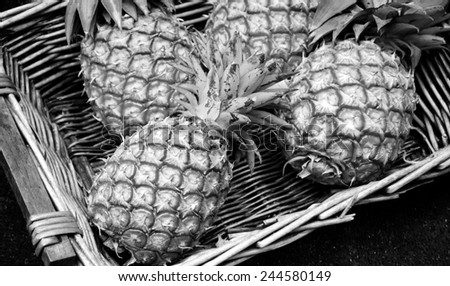 Pineapples in wicker basket at organic farmers market in Paris (France). Aged photo. Black and white. - stock photo