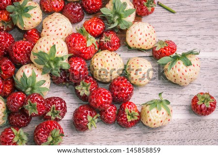 Pineberries and strasberries, against wooden background - stock photo