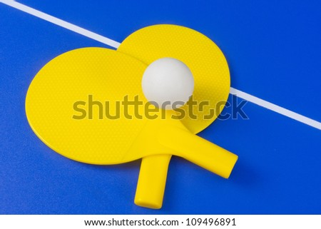 Ping Pong ball and paddles on game table - stock photo