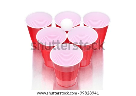 Ping pong ball resting on a group of red plastic cups arranged for playing Beer Pong isolated on a white background with reflection. - stock photo