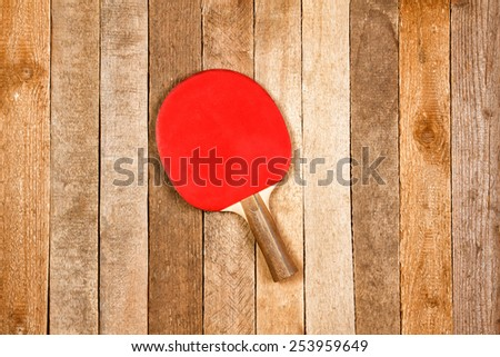 Ping pong paddle against wooden background - stock photo