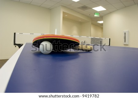 Ping Pong Paddle on Blue Table - stock photo
