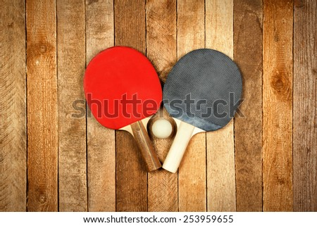 Ping pong paddles and ball on wooden background - stock photo