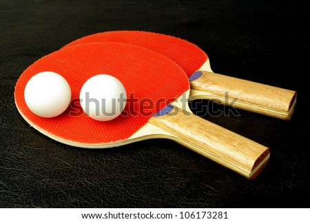 Ping-pong paddles and balls on black - stock photo