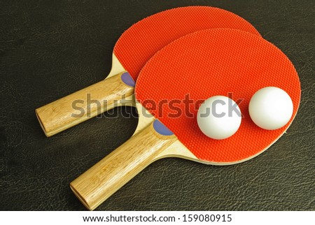 Ping pong paddles and balls on black  - stock photo
